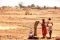 Tribal woman pumping water from hand pump, Nandgaon, Atgaon, Maharashtra, India, Asia