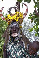 Mursi Tribe headdress woman with baby Omo Valley Ethiopia.