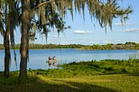 Husband and wife fishing from a small boat together for bass fish on Hardee Lake County Park Florida campground.