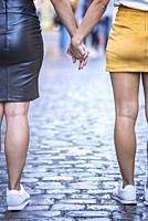 Couple of women walking down the street holding hands.