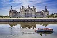 Chambord Castle with some people boating on the canal that surrounds it.