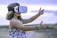 Little girl playing with a virtual reality glasses.