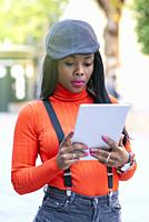 Beautiful young woman with dark skin using a tablet in the middle of the street.