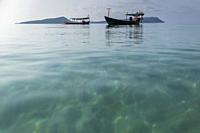 Low perspective view of traditional fishing boats at the Tui beach of Koh Rong Island in Cambodia.