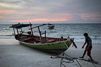 A local fisherman with his boat moored in the beach of Koh Rong island, Cambodia.