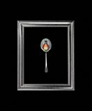 Still life with a Strawberry Rasberry and a Blueberries on a spoon in the frame.