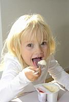 Little blond girl eating yoghurt, Sweden.