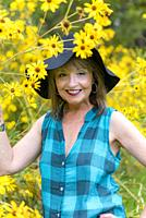 A 51 year old woman standing in front of yellow autumn flowers, wearing a black hat looking at the camera, outdoors.