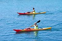 two mature men paddle on a kayak along the sea coast.