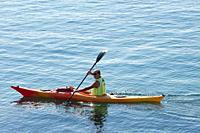 a man paddle on a kayak along the sea coast.