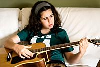 Girl practicing chords on acoustic guitar at home sitting on bed.