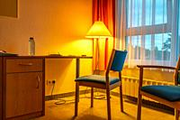 A room filled with golden light from yellow floor lamp with two blue chairs and a window with orange coloured curtains.