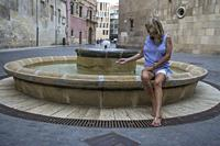Female tourist dips her hand in a water fountain in the City of Murcia Spain.
