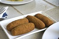 Four cod fish croquettes on square plate Spain.