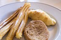 Breakfast plate with churros torrija and croissant Spain.