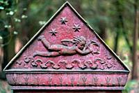 Triangular part of a tombstone showing a flying cherub on red background with stars in the sky at Suedwestfriedhof cemetery, Stahnsdorf, Germany