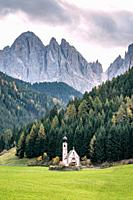 St. Johann in Ranui - a small church with onion tower in front of the Dolomite mountais Geisler massif in Santa Maddalena, Italy.