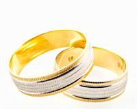 Close-Up Of Gold Wedding Rings Against White Background.