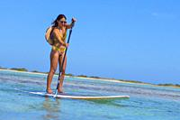 young woman practising paddle board or sup in tropical Caribbean sapphire crystal clear calm waters.