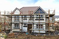 New build house under construction and surrounded by scaffolding, Stewart Milne building site near Troon, Ayrshire, Scotland.