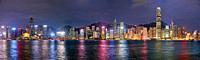 Panorama of high-rise waterfront buildings illuminated at night. Hong Kong, China.