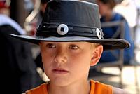 Portrait on boy, ten years, wearing a black cowboy hat at High Chaparrall amusement park in Småland, Sweden.
