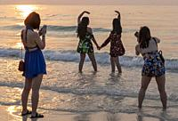 Young women take posed photos, Sai Kaew Beach, Ko Samet, Thailand.