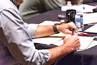 Man taking notes in a meeting.