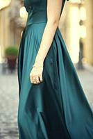 Side view close up of a woman wearing green evening dress standing outdoors.