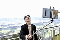 Korean tourist man taking selfie at mount Untersberg with view at Salzburg, Austria, Europe.