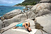 Practicing Yoga on rocks in Six Senses Zil Pasyon luxury hotel. Felicite island Seychelles.