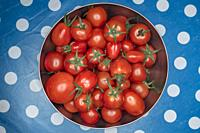 Top view of homegrone cherry tomatoes in a bowl- colour palette.