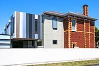 Starkly modern extension of a Victorian-era brick house in suburban Melbourne, Australia.