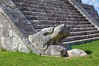 Serpent head at the base of the main staircase of the central Castle at the Mayan Chichen Itza site in Mexico.