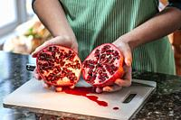A cross secetion of a half Pomegranate, expsosing rind and seeds.