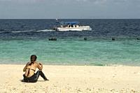 Woman in wetsuit sitting on beach with dive boat in background, Sipadan Island, Sabah, Borneo, Malaysia, Celebes Sea.