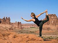 An attractive young woman practices yoga at the La Sal Mountains Overlook in Arches National Park near Moab, Utah. In the background are the Courthous...
