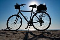 A bike parked at the beach on a clear day,.