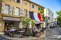 Small french village cafes with French flag in Provence region of Southern France.