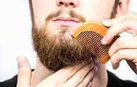Closeup of a young man styling his long beard with a comb while standing alone in a studio against a white background beauty.