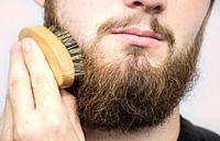 Hand of barber brushing beard. Barbershop customer,front view. Beard grooming tips for beginners. close-up.