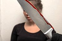 young woman holding bloody knife with black glove , crime scene killing scary.