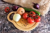 Fresh vegetables - onions, tomatoes, cucumber on a cutting board.