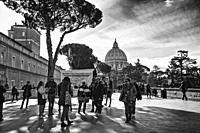 People walking in the Vatican Museum, in the background the dome of the Basilica of St Peter in Rome (Italy) in black and white.