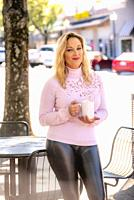 A pretty 40 year old blond woman on a city street, holding a cup of coffee and looking at the camera.