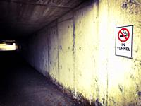 A no smoking sign in words and graphic image on the entrance to a short tunnel on a college campus in Ontario, Canada. The sign is now redundant becau...