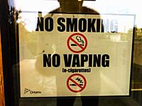 A reflected selfie in front of a glass door which displays ´No Smoking´ and ´No Vaping´ signs in words and pictograph.