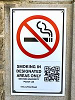A smoking regulation, complete with words, pictograph, and a QR code on the wall of a college campus, Ontario, Canada. The sign is mainly of historica...