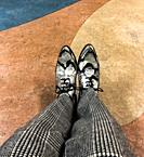 A gentleman´s fancy shoes and pants resting on a floor with a geometric pattern.