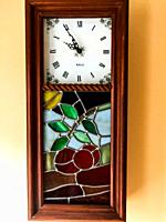 An antique clock with a floral pattern made from stained glass pieces hangs on a wall, Nova Scotia, Canada